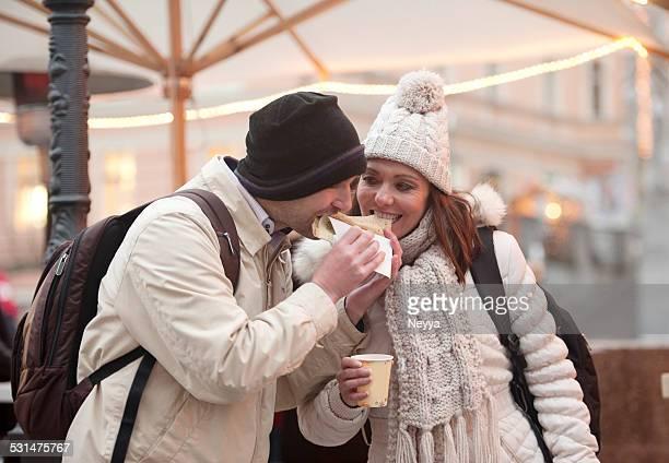 Couple dans un marché de Noël à Ljubljana manger des crêpes