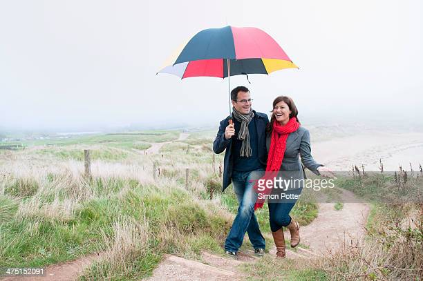 Couple on coast walk carrying umbrella, Thurlestone, Devon, UK