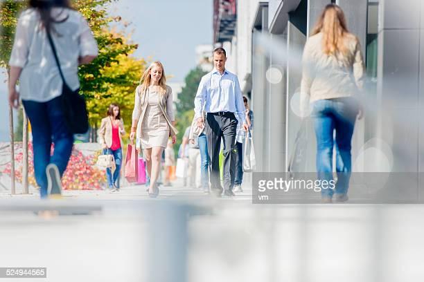 Couple sur une rue de ville bondées après une journée de Shopping