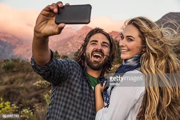 Couple on hillside taking selfie