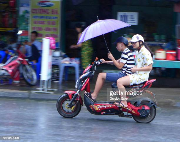 Couple on motorcycle brave rain shower with umbrella