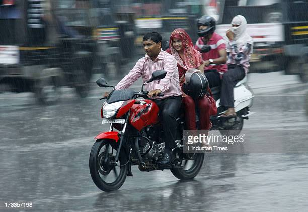 A couple on motorcycle moves during monsoon rains on July 12 2013 in Gurgaon India India's monsoon rains were 5 percent below average in the week...