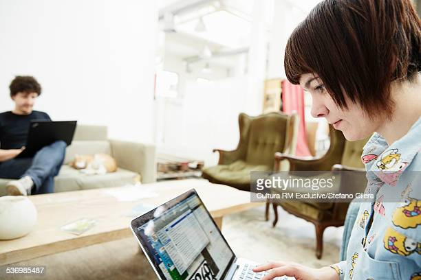 Couple on opposite sofas typing on laptops