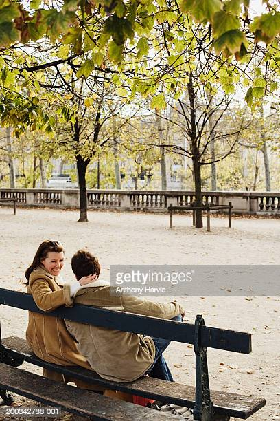 Couple on park bench, woman with arm around man, rear view