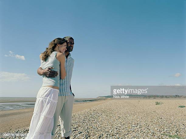 Couple on pebble beach, man with arm around woman, smiling