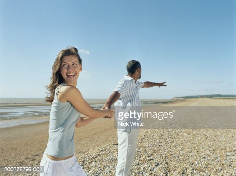 Couple on pebble beach, woman holding on to man's hand, laughing : Stock Photo