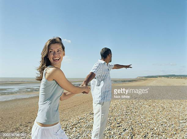 Couple on pebble beach, woman holding on to man's hand, laughing