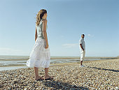 Couple on pebble beach, woman looking at man with hands in pockets