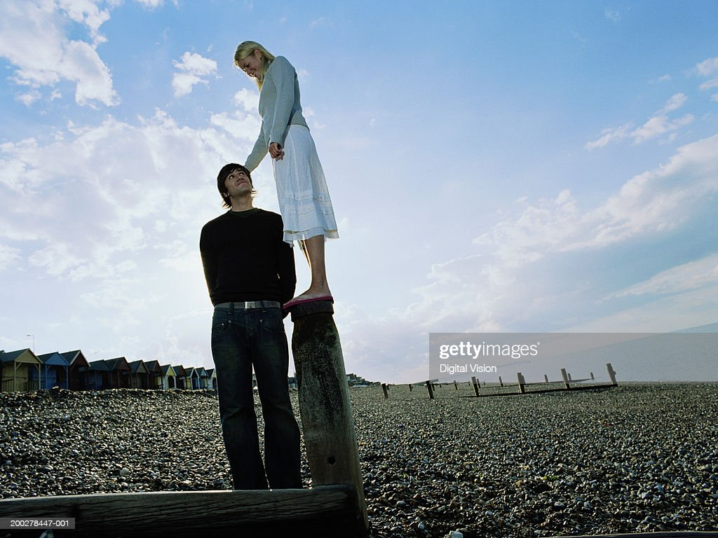 Couple on pebbled beach, man looking up at woman standing on groyne : Stock Photo