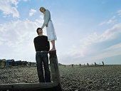 Couple on pebbled beach, man looking up at woman standing on groyne