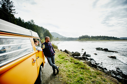 Couple on road trip in van parked by ocean
