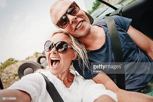 Couple on roadtrip in cabriolet car through europe