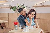 man hugging upset girlfriend while having romantic date in coffee shop
