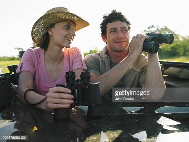 Couple on safari in 4x4 holding binoculars, smiling