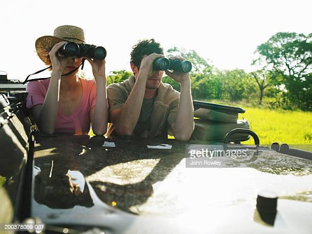 Couple on safari in 4x4 using binoculars