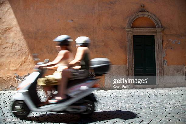 Couple on scooter passing ancient doorway in Rome