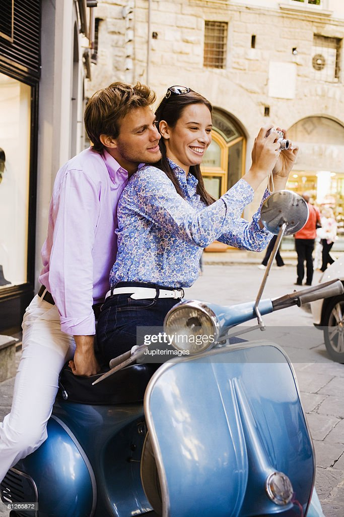 Couple on scooter with digital camera