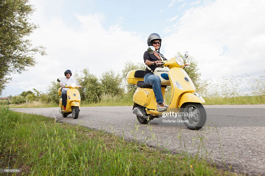 Couple on scooters riding down rural road