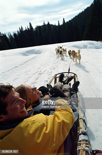 Couple on sledge being pulled by Huskies, over shoulder view