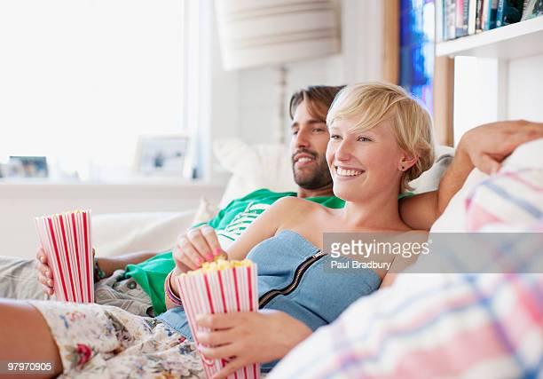 Coppia sul divano mangiando popcorn e guardare la TV