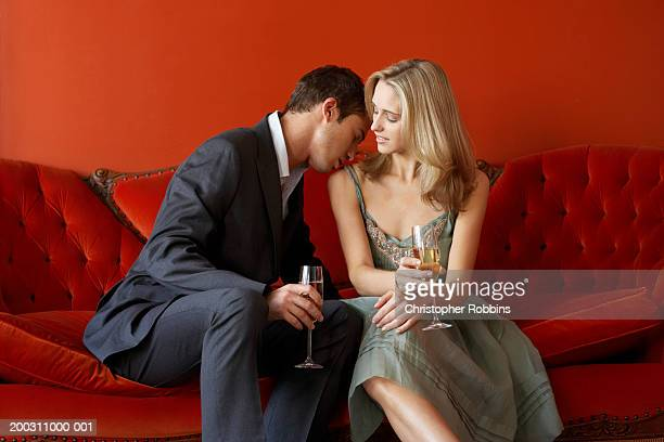 Couple on sofa holding champagne glasses, man kissing woman's shoulder