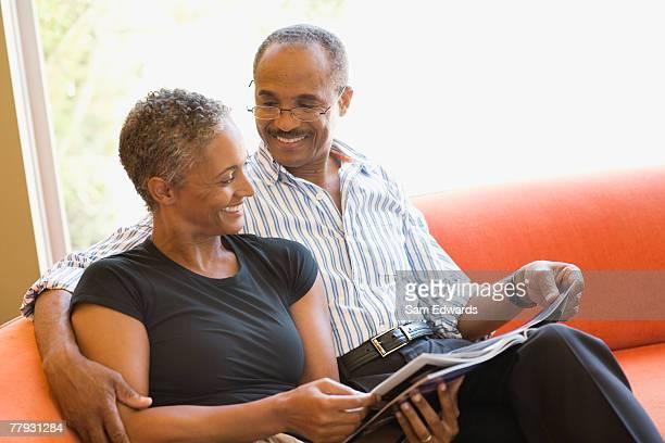 Couple sur canapé en maison moderne avec un magazine