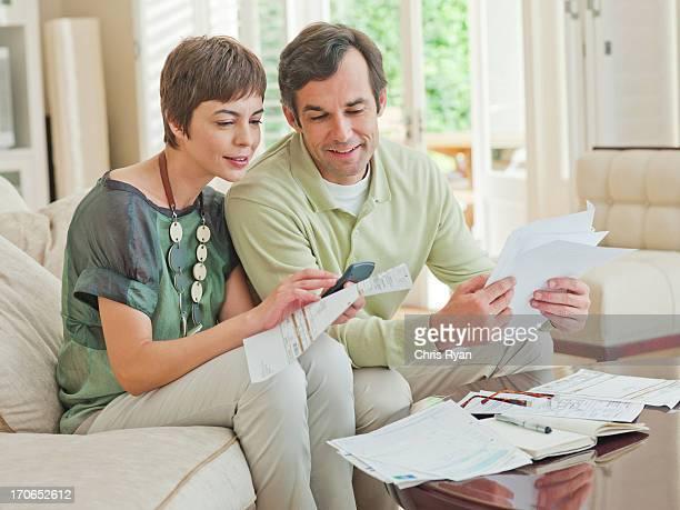 Couple on sofa paying bills