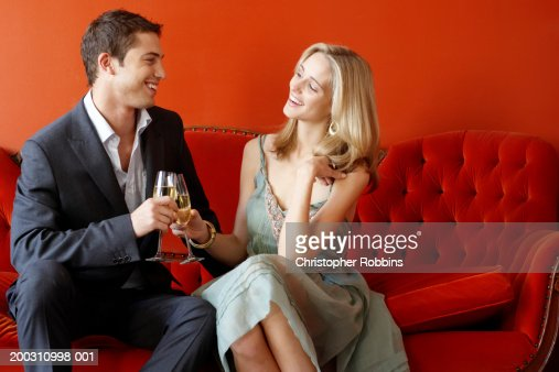 Couple on sofa toasting with glasses of champagne, smiling : Stock Photo