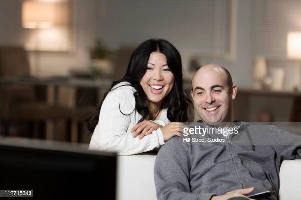 Couple on sofa watching television together