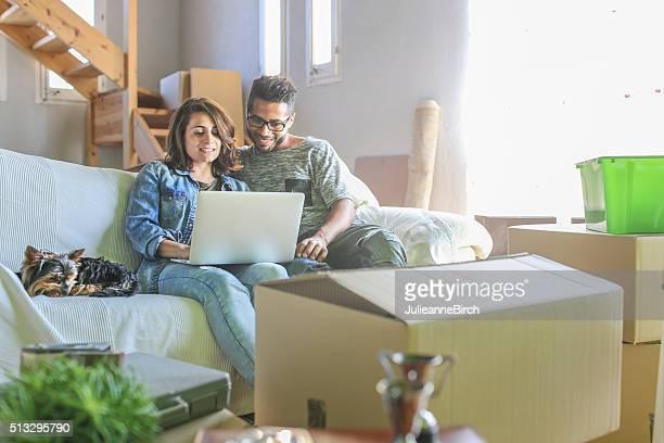 Paar auf Sofa mit Kästen um Sie