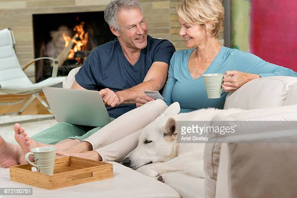 Couple on sofa with dog online shopping with laptop
