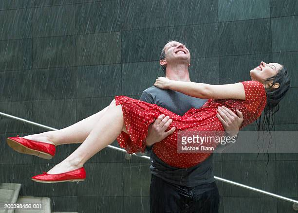 Couple on steps in rain, man carrying young woman, eyes closed