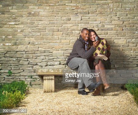 Couple on stone bench in front of brick wall, looking at mobile phone