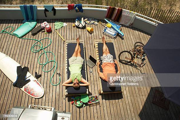 Couple on sunbeds on deck surrounded by beach equipment, elevated view