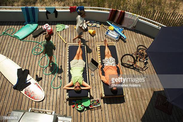 Couple on sunbeds on deck with children running round (10-11), elevated view