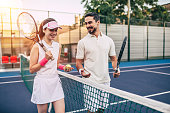 Young couple on tennis court. Handsome man and attractive woman are playing tennis.