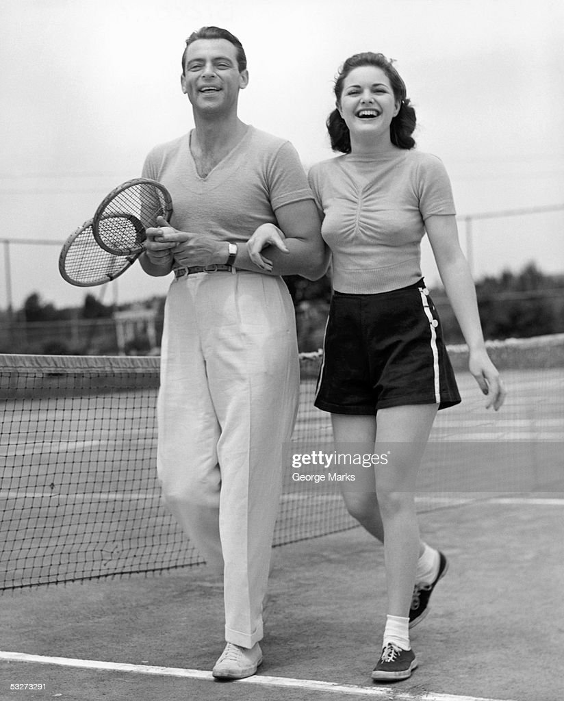 Couple on tennis court with tennis racquets : Stock Photo