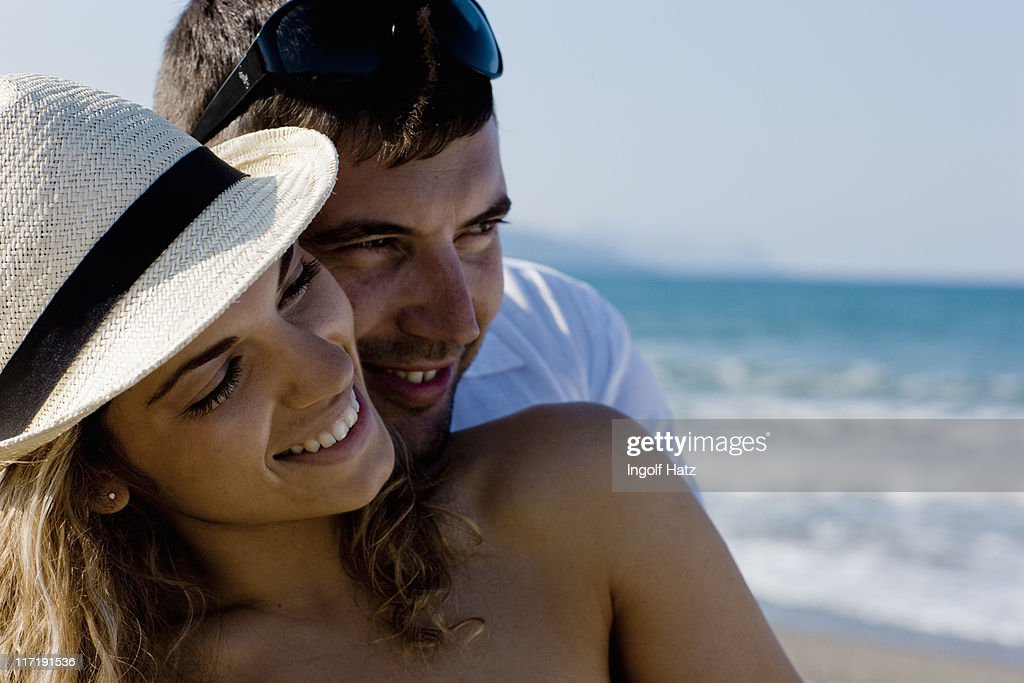 couple on the beach cuddling : Stock Photo