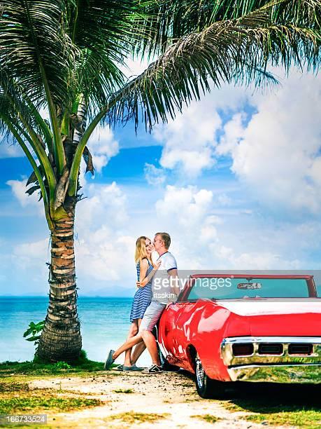 Couple on the beach with retro car