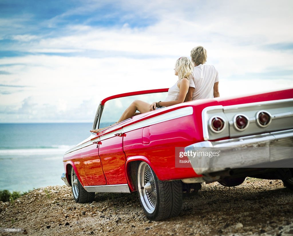 Couple on the cliff sitting in car : Stock Photo