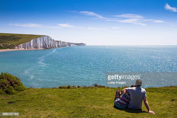 A couple on the cliffs looking toward the chalk cliffs known as the Seven Sisters