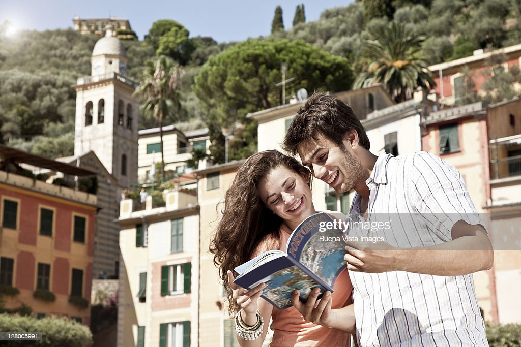 Couple on vacation reading tourist guide. : Stock Photo