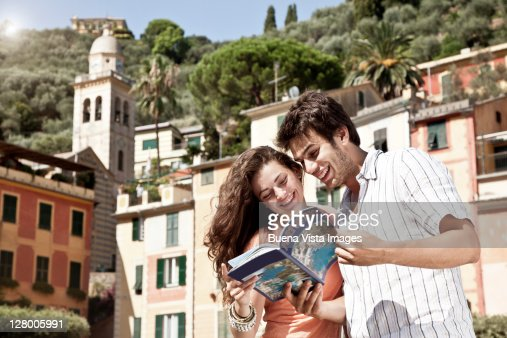 Couple on vacation reading tourist guide. : Stock-Foto