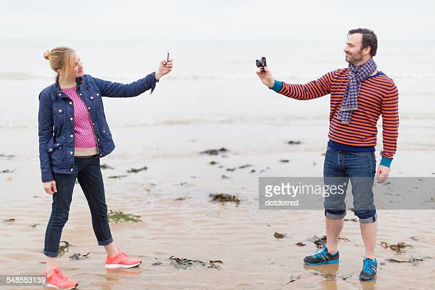 Couple on wet beach, taking photographs of each other