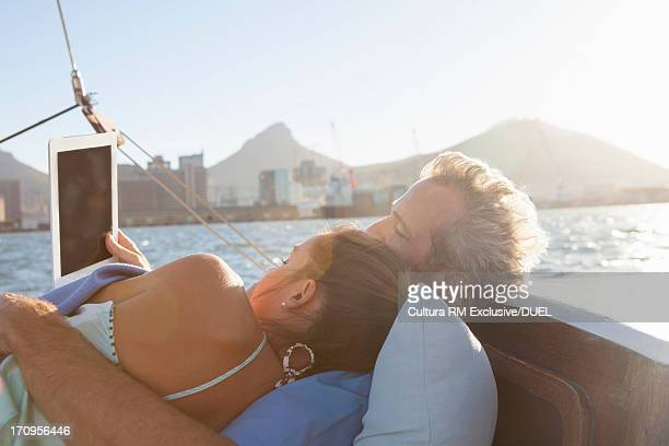 Couple on yacht with digital tablet
