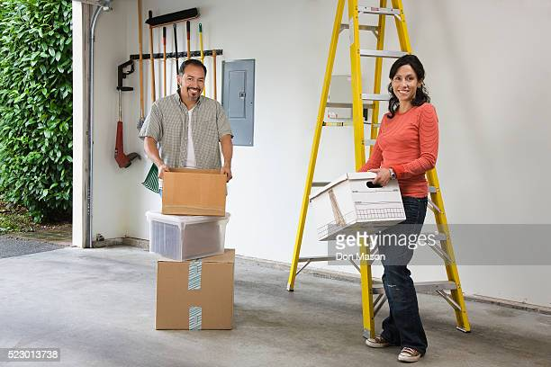 Couple Organizing Boxes in Garage