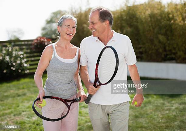 Couple outdoors holding tennis rackets