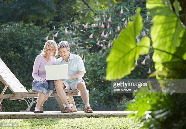 Couple outdoors in yard with laptop