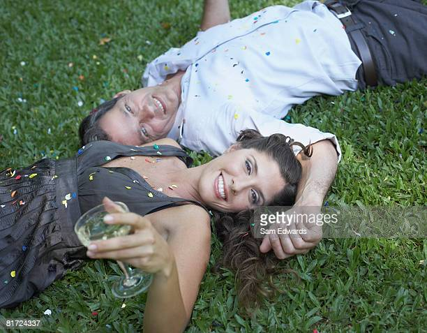 Couple outdoors lying on grass with white wine and confetti smiling