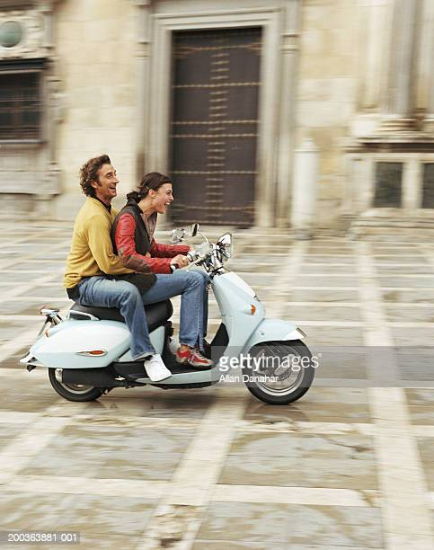 Couple outdoors on moped, side view